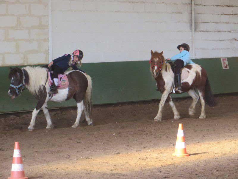 jeunes filles faisant de l'équitation en manège en colo d'équitation de printemps