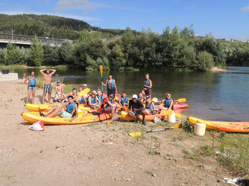 groupe d'ados se préparant à faire du canoe kayak en colo au Portugal