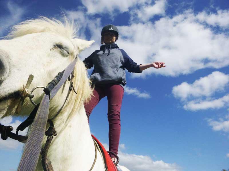 Enfant debout sur son cheval en colonie de vacances équitation