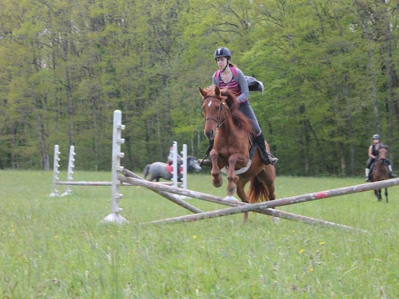 Enfant faisant des courses d'obstacle à cheval en colonie de vacances au printemps