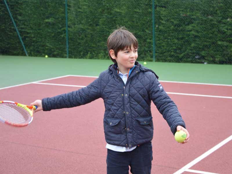 Enfant apprenant à faire du tennis en colonie de vacances multiactivités