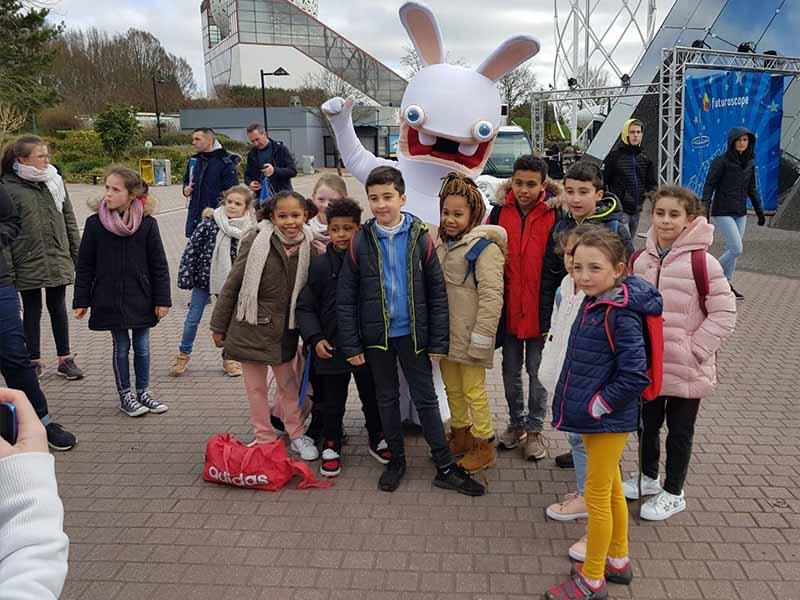 Groupe d'enfants au Futuroscope avec une statue de lapin crétin en colonie de vacances de printemps
