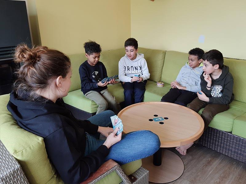 enfants jouant aux cartes en colonie de vacances ce printemps