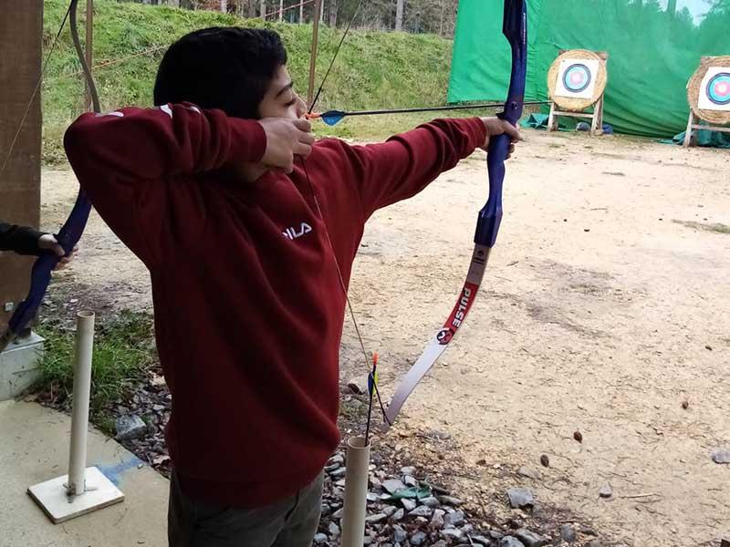 Enfant faisant du tir à l'arc en colo au printemps