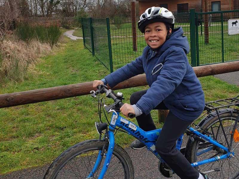 enfant faisant du vélo en colonie de vacances ce printemps