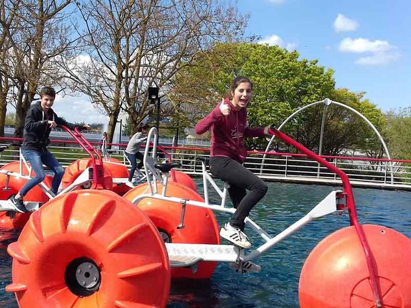 adolescente sur un vélo sur l'eau en colonie de vacances de printemps