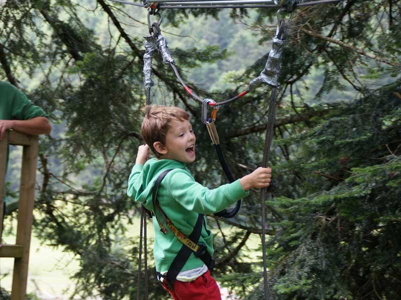 Enfant faisant de l'accrobranche en colonie de vacances d'été