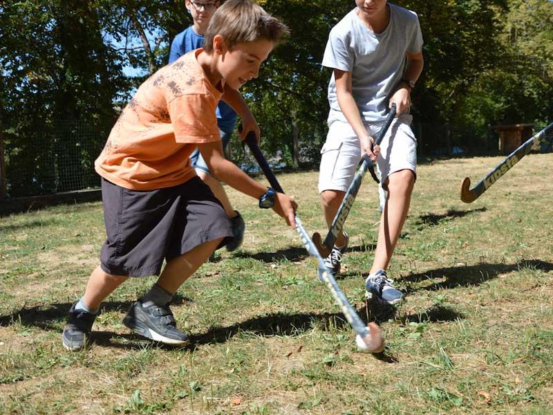 Enfants jouant au hockey sur gazon en colonie de vacances d'été