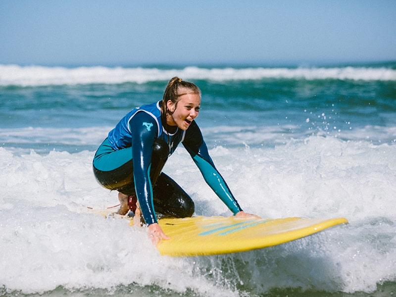 Surfeuse ado qui apprend à pratiquer le surf au Maroc lors d'une colonie de vacances au printemps