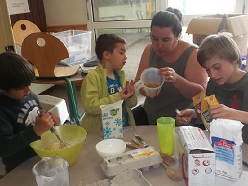 Enfants et leur animatrice de colonie de vacances apprenant à cuisiner
