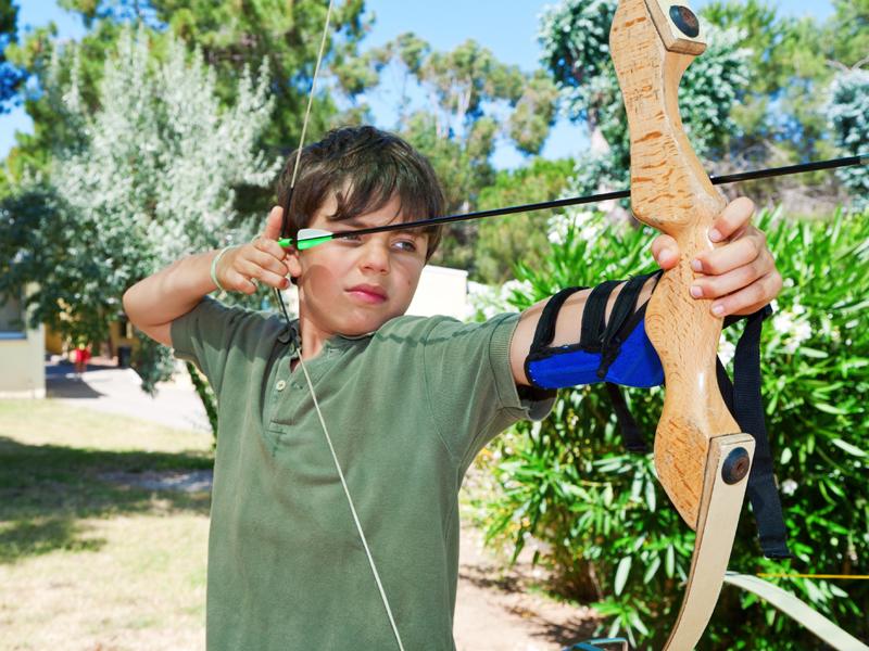 Enfant de 10 ans faisant du tir à l'arc en colonie de vacances à la campagne
