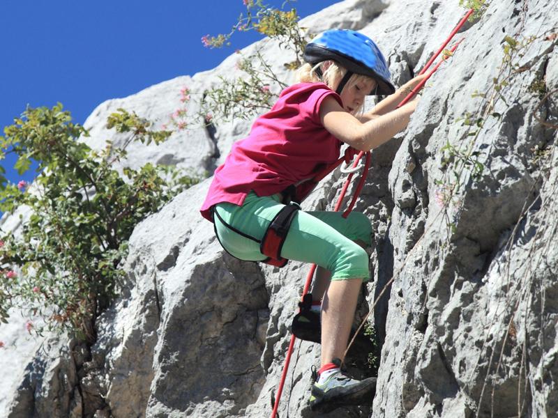 Enfant pratiquant l'escalade en colonie de vacances au printemps