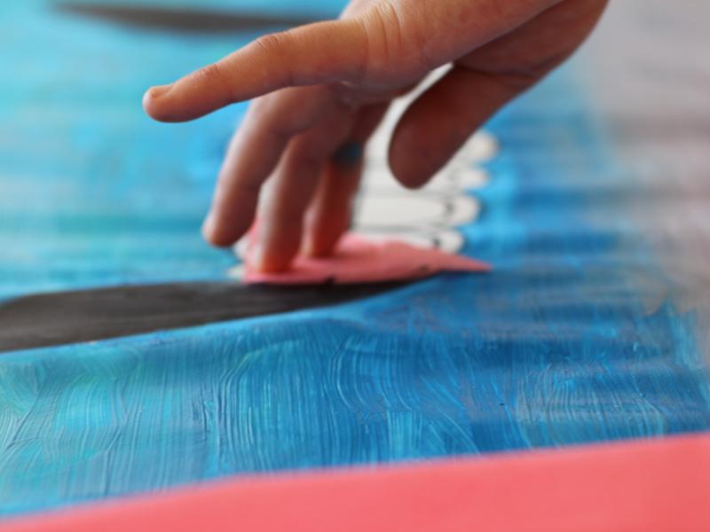 Main d'enfant peignant une fresque en colo