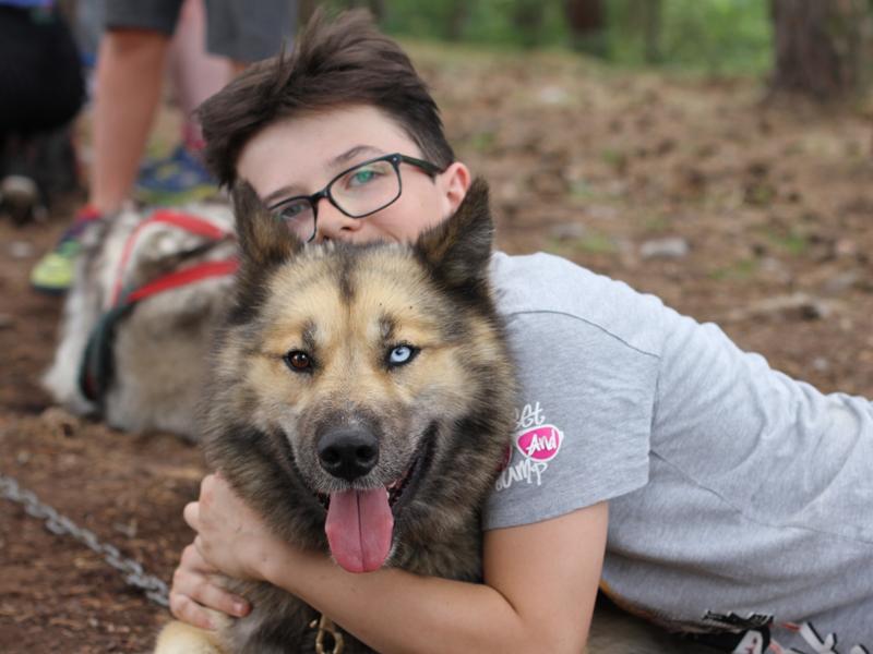 Portrait d'un enfant avec son chien en cani-rando