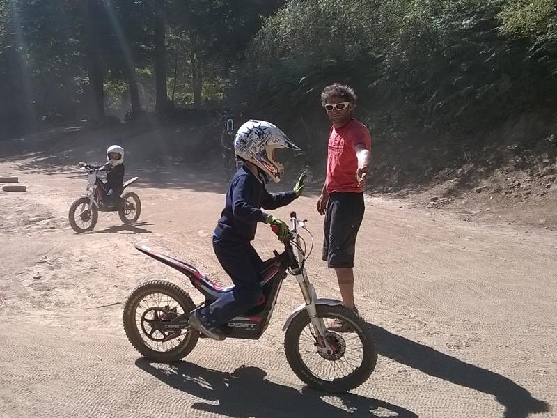 Enfant roulant à moto guidé par l'animateur de colo
