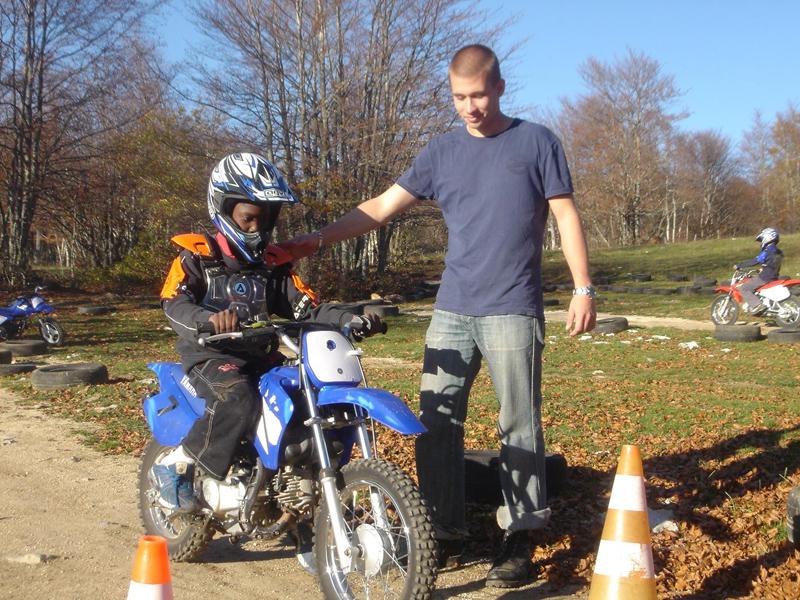 Animateur apprenant à l'enfant à conduire une moto