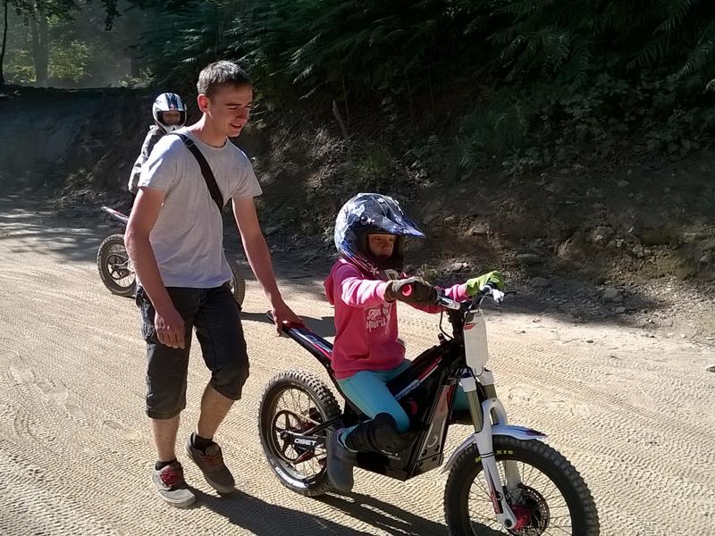 Enfant apprenant à faire de la moto grâce à son animateur de colonie