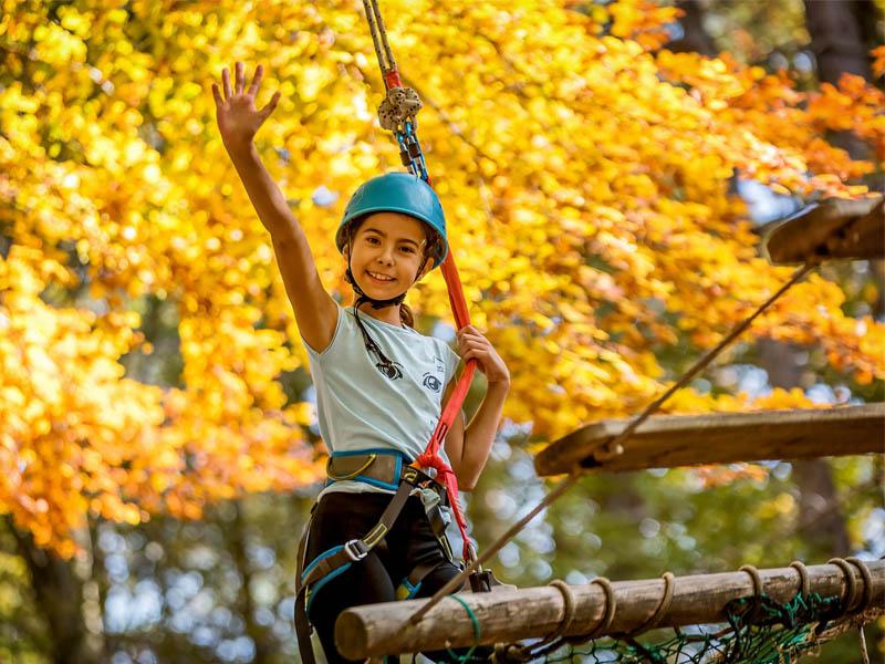 Jeune fille pratiquant l'accrobranche en colonie de vacances à Eco park