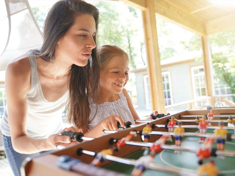Enfant et son animatrice de colonie de vacances jouant au babyfoot en vacances