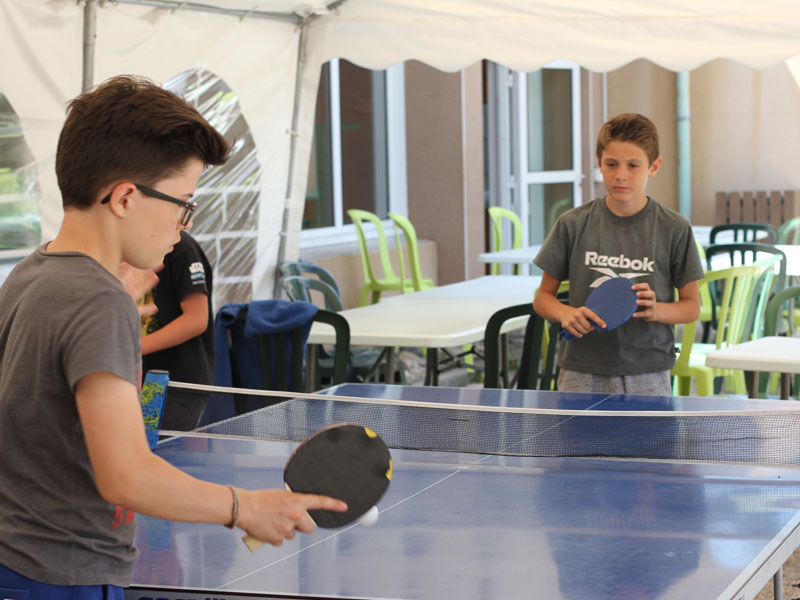 Enfants jouant au tennis de table en colo