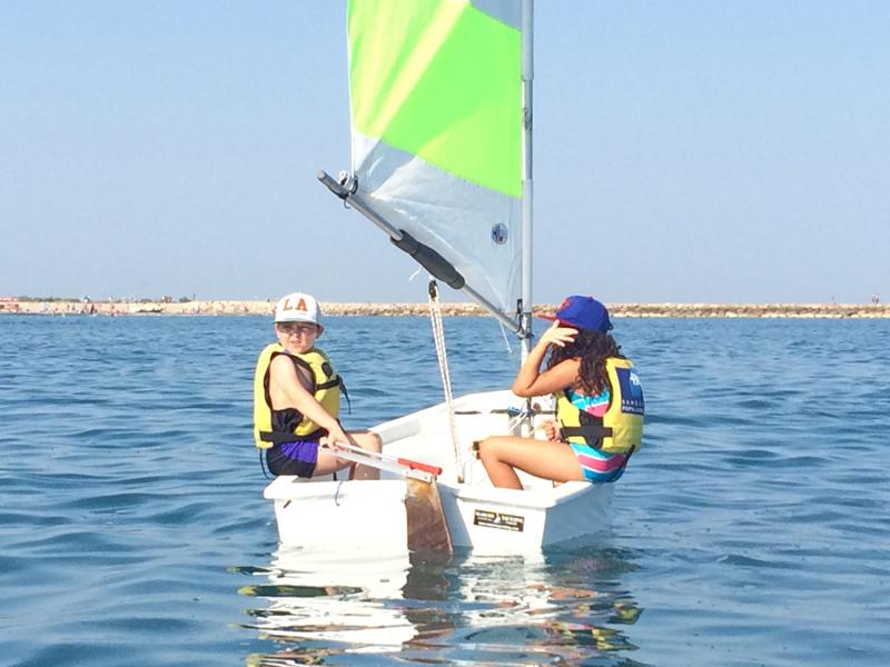 Enfants sur un optimist en mer