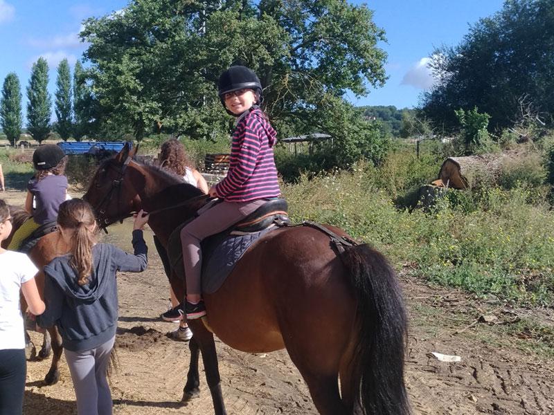 Enfants pratiquant l'équitation en colonie de vacances