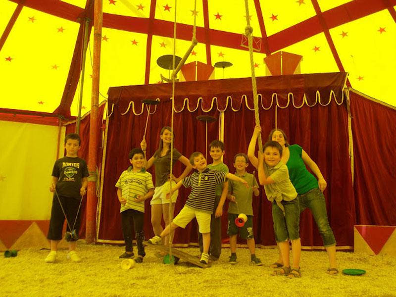 Enfants sous un chapiteau de cirque en colonie de vacances