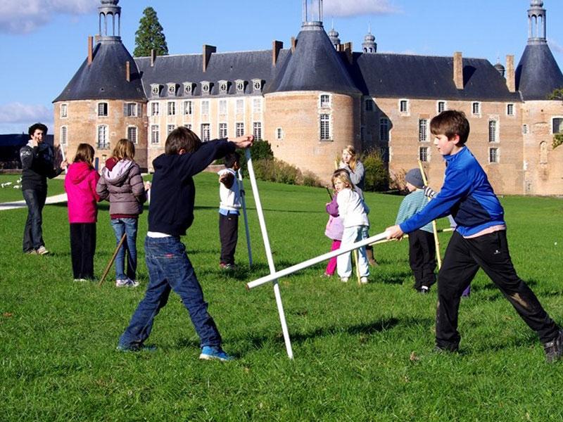 Enfants jouant avec des épées en bois en colonie de vacances