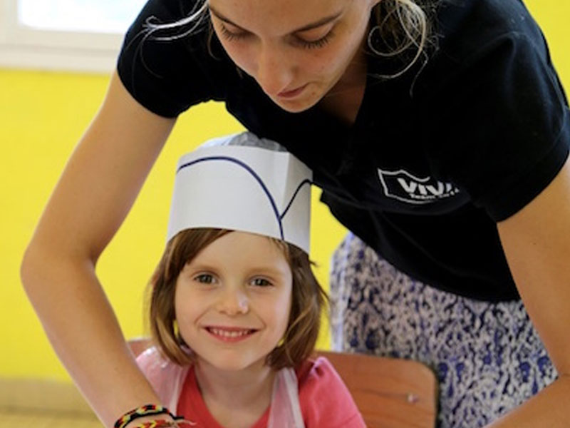 Jeune enfant apprenant à faire la cuisine en colo
