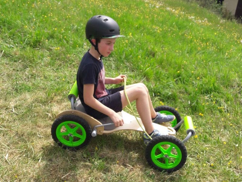 Enfant sur une luge à roulette en colo