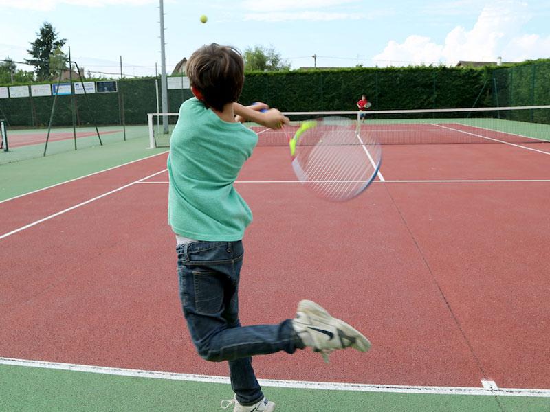 Enfant jouant au tennis en colonie de vacances
