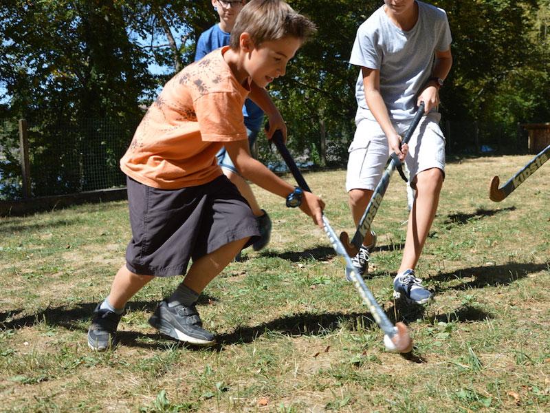 Enfants jouant ensemble au hockey sur gazon en colonie de vacances