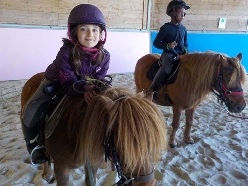 Enfants avec des poneys en colonie de vacances
