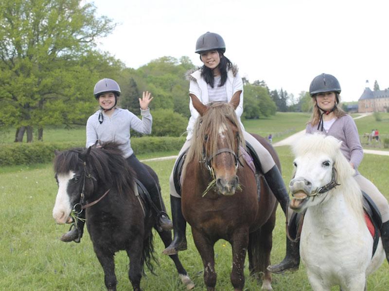 Enfants à cheval en colonie de vacances pour apprendre l'anglais