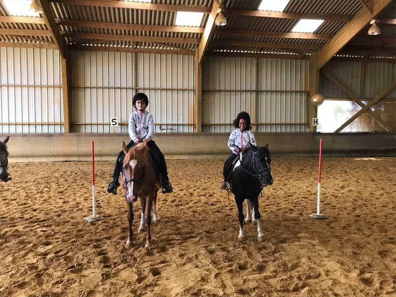 deux jeunes filles faisant de l'équitation en colo cet automne