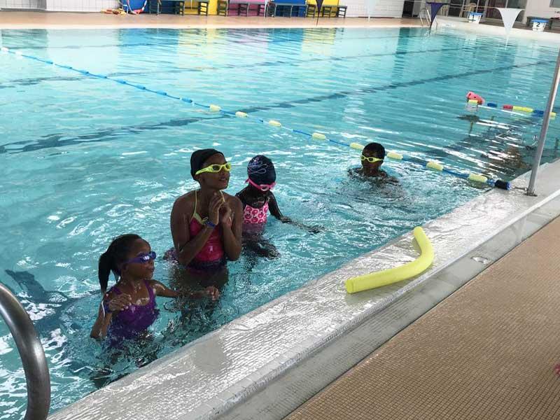 groupe d'enfants dans la piscine apprenant à nager avec des frites en colonie de vacances