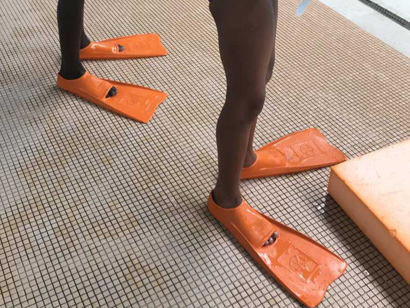 Pieds d'enfants avec des palmes pour apprendre à nager en colonie de vacances
