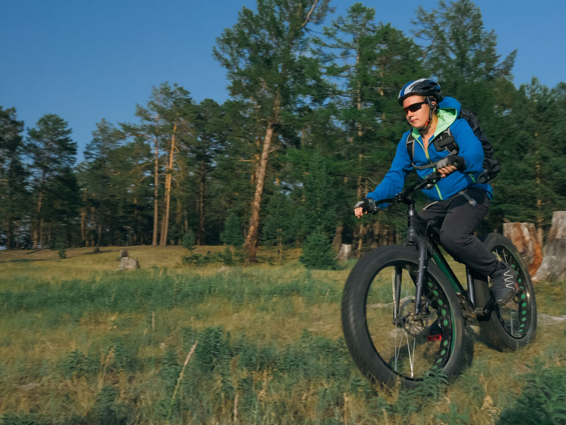 ado pratiquant le fat bike en colonie de vacances à la montagne