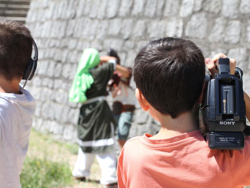 enfant tenant sur son épaule une caméra lors de la réalisation d'un court métrage en colonie de vacances