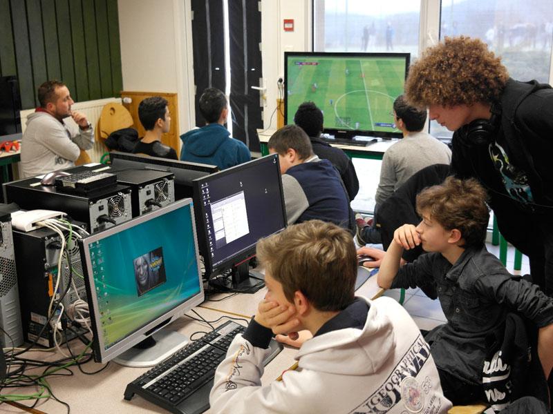 enfants et leur animatrice jouant aux jeux vidéo en colonie de vacances pour geek à la montagne
