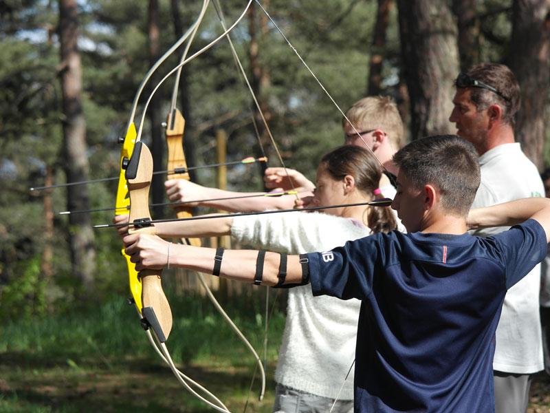 groupe d'enfant apprenant à faire du tir à l'arc cet automne en colonie de vacances à la montagne