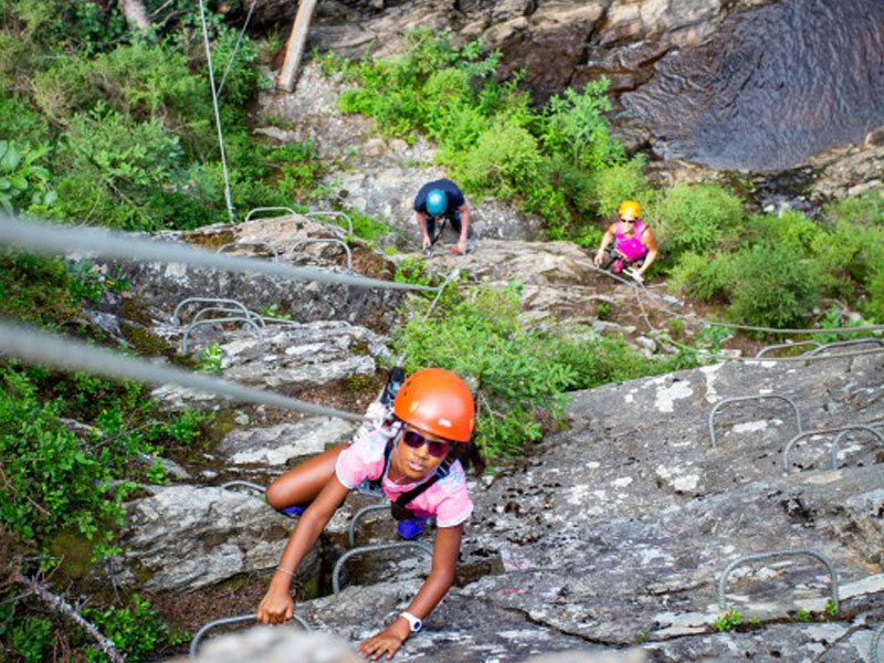 Enfant faisant de la via ferata en colonie de vacances à la montagne