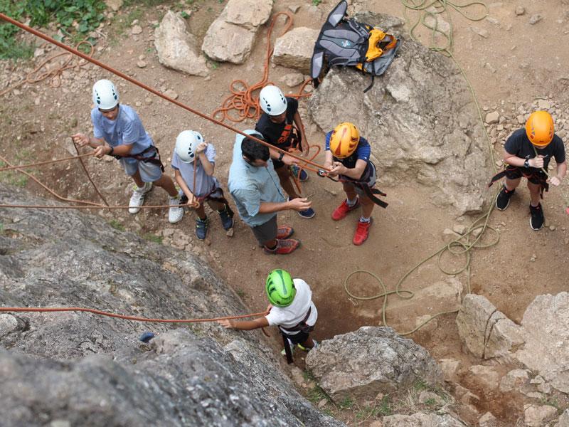 groupe d'enfants pratiquant la descente en rappel en colonie de vacances à la montagne