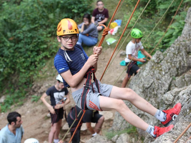 Enfant faisant de l'escalade en colonie de vacances à la montagne