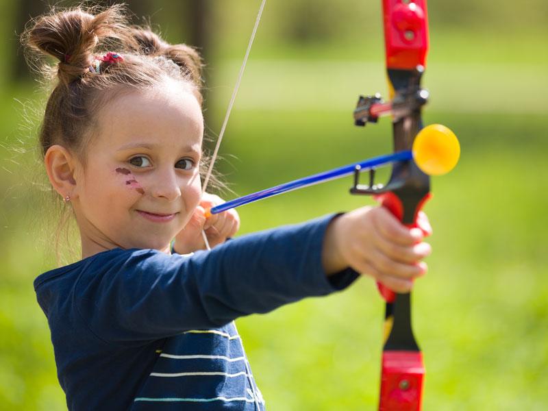 fillette apprenant à faire du tir à l'arc sécurisé en colo cet automne