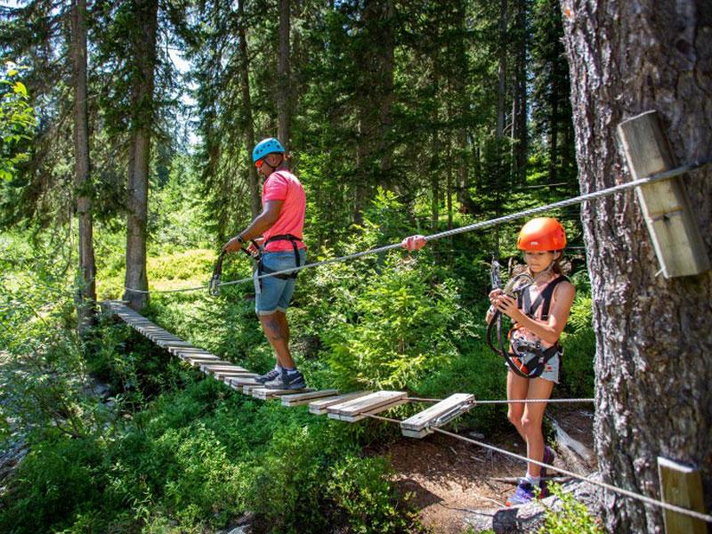 enfants faisant de l'accrobranche à la montagne en colonie de vacances