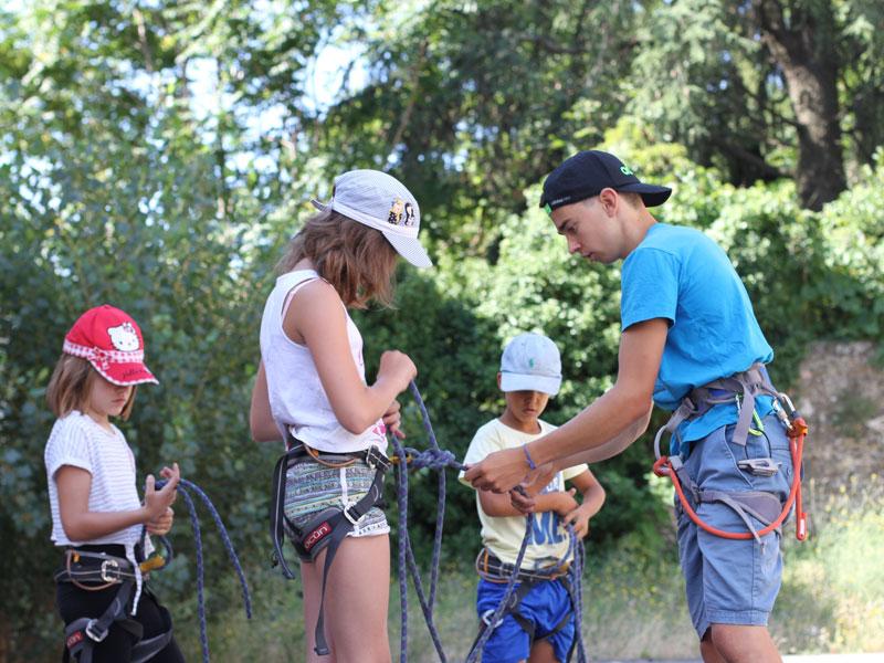 enfants apprenant à mettre leur baudrier pour faire de l'escalade en colonie de vacances