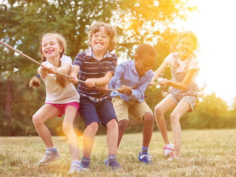 quatre enfants jouant à la corde en colonie de vacances à la montagne