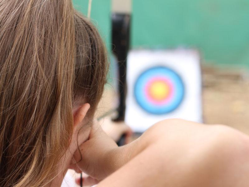 jeune fille se concentrant sur la cible avec son arc lors d'une séance de tir à l'arc en colonie de vacances à la montagne