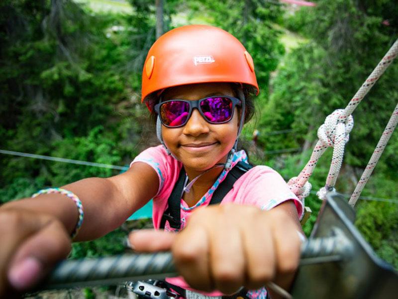 portrait d'une fillette faisant de l'accrobranche en colonie de vacances cet automne à la montagne